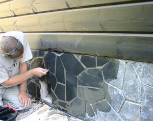 Asennuksen jälkeen saumat täytetään. Työn alla mustan liuskesokkelin viimeistely.